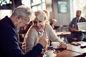 Close up of a happy senior couple having coffee in a cafe