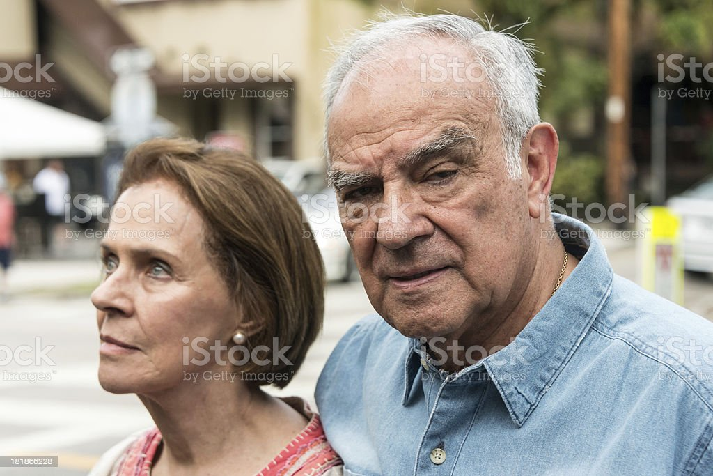 "Senior Couple (focus on man) ""Senior couple, a caucasian woman and a hispanic man,  outside. With the man in the foreground in focus and the woman in the background out of focus."" 65-69 Years Stock Photo"