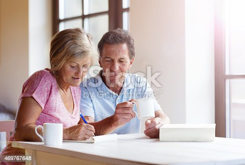 Happy senior couple sitting at the table making plans and drinking coffee in their living room.