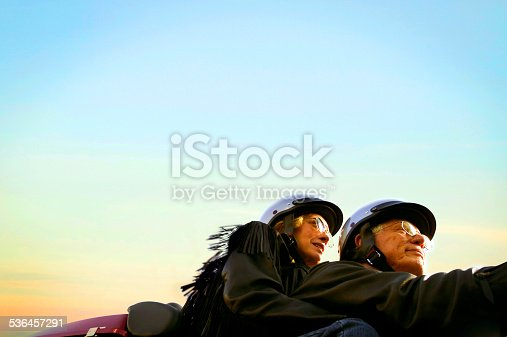A happy senior couple riding on a motorcycle.