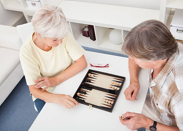 senior couple playing backgammon - backgammon stock pictures, royalty-free photos & images