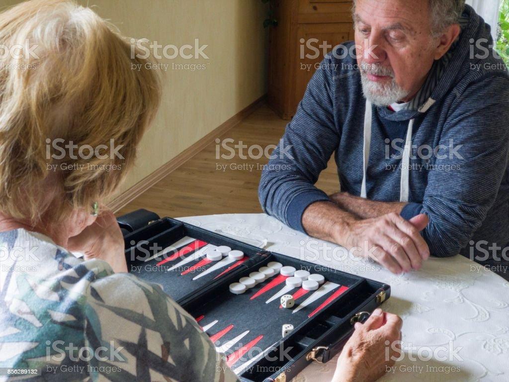 Senior couple playing backgammon stock photo