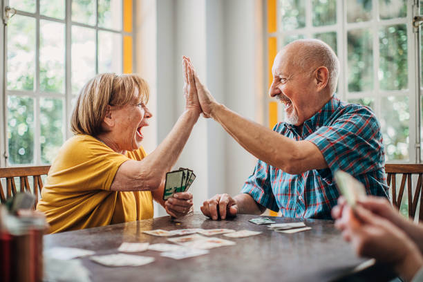 Senior couple playing cards in nursing home stock photo