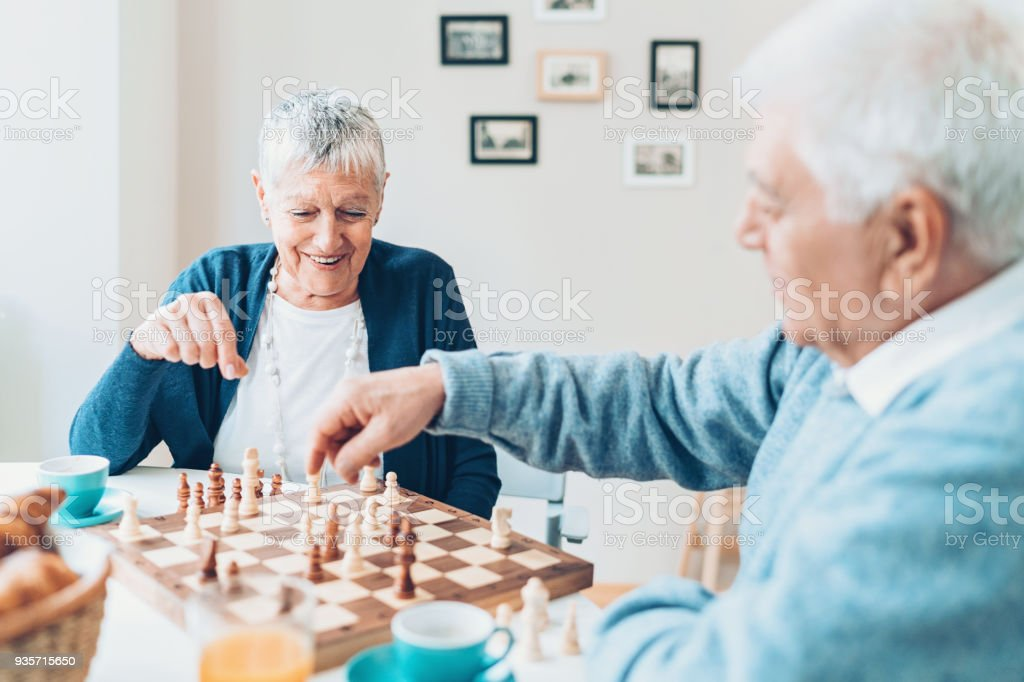 Senior couple playing chess at home stock photo
