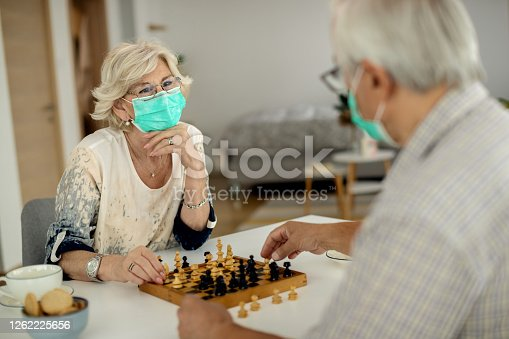 Senior woman and her husband wearing protective face masks while playing chess at home.