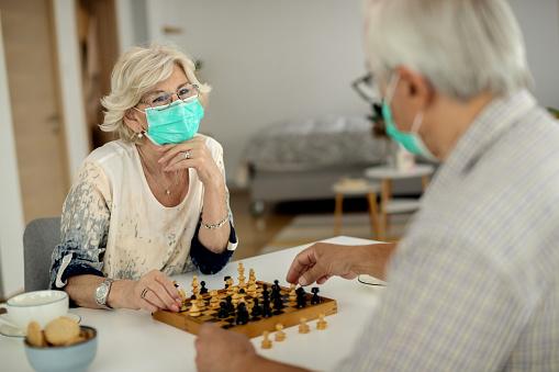 Senior couple playing chess during home quarantine due to coronavirus epidemic.