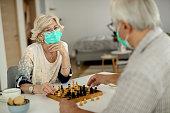 istock Senior couple playing chess during home quarantine due to coronavirus epidemic. 1262225656