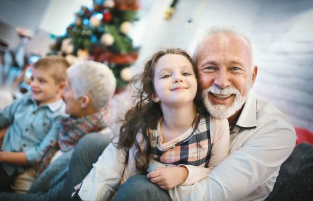 Senior couple playing with grandchildren. stock photo
