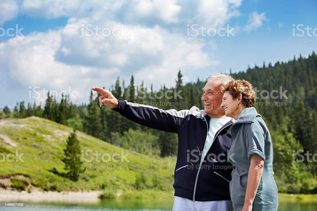 Senior couple pointing and smiling outdoors by a lake stock photo