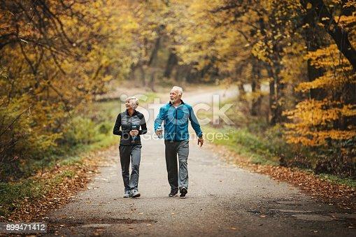 istock Senior couple power walking in a park. 899471412