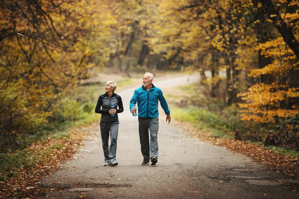 Senior couple power walking in a park. stock photo
