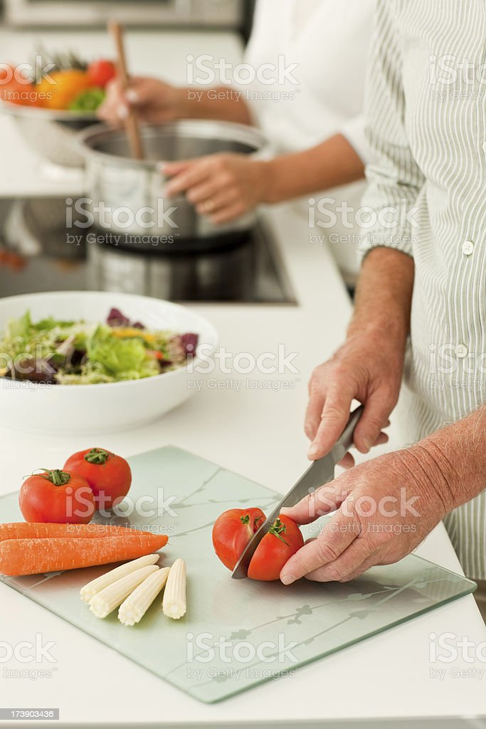 senior couple preparing food at the kitchen royalty-free stock photo