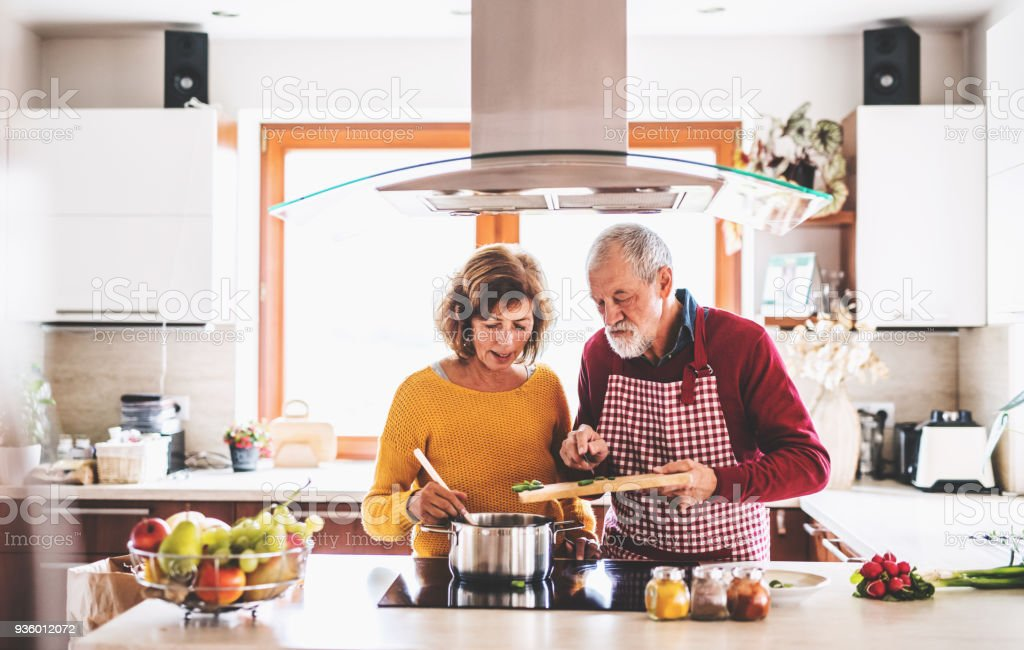 Senior couple preparing food in the kitchen. stock photo