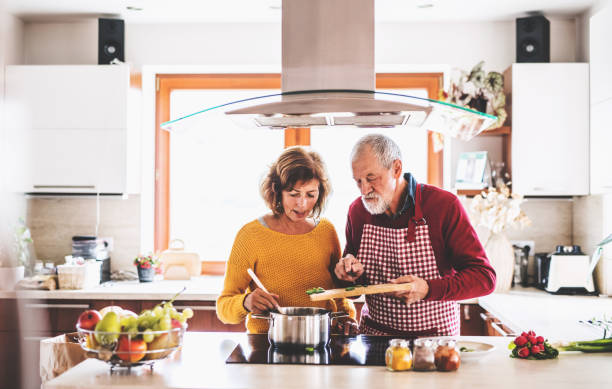 senior couple preparing food in the kitchen. - home cooking stock photos and pictures