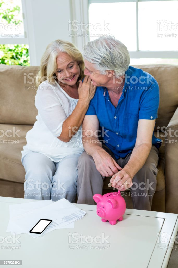 Senior couple putting coin in piggi bank while sitting at home stock photo