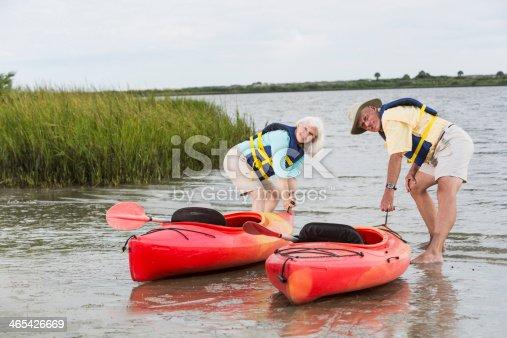 istock Senior couple putting kayaks in water 465426669