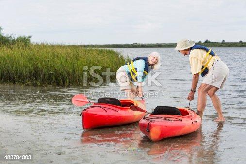 istock Senior couple putting kayaks into water 483784803