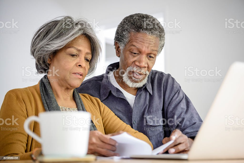 Senior couple reading document with laptop stock photo
