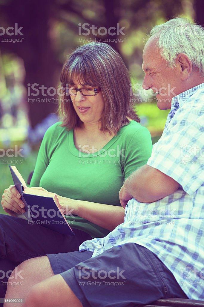 Senior couple reading in park royalty-free stock photo
