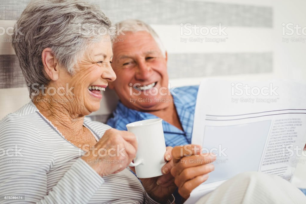 Senior couple reading newspaper stock photo