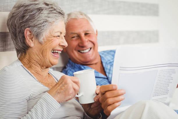 altes paar lesen zeitung - seniorenwohnungen stock-fotos und bilder