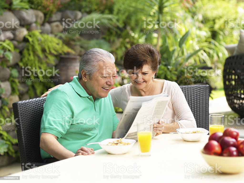 Senior couple reading newspaper while eating breakfast royalty-free stock photo