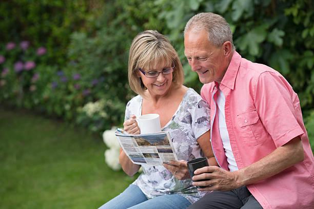 senior couple reading the newspaper - garden types stock-fotos und bilder