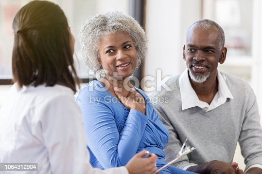 A smiling senior man and his relieved wife sit beside an unrecognizable female doctor and listen as she holds a clipboard and shares good news.  The woman puts her hand on her heart.
