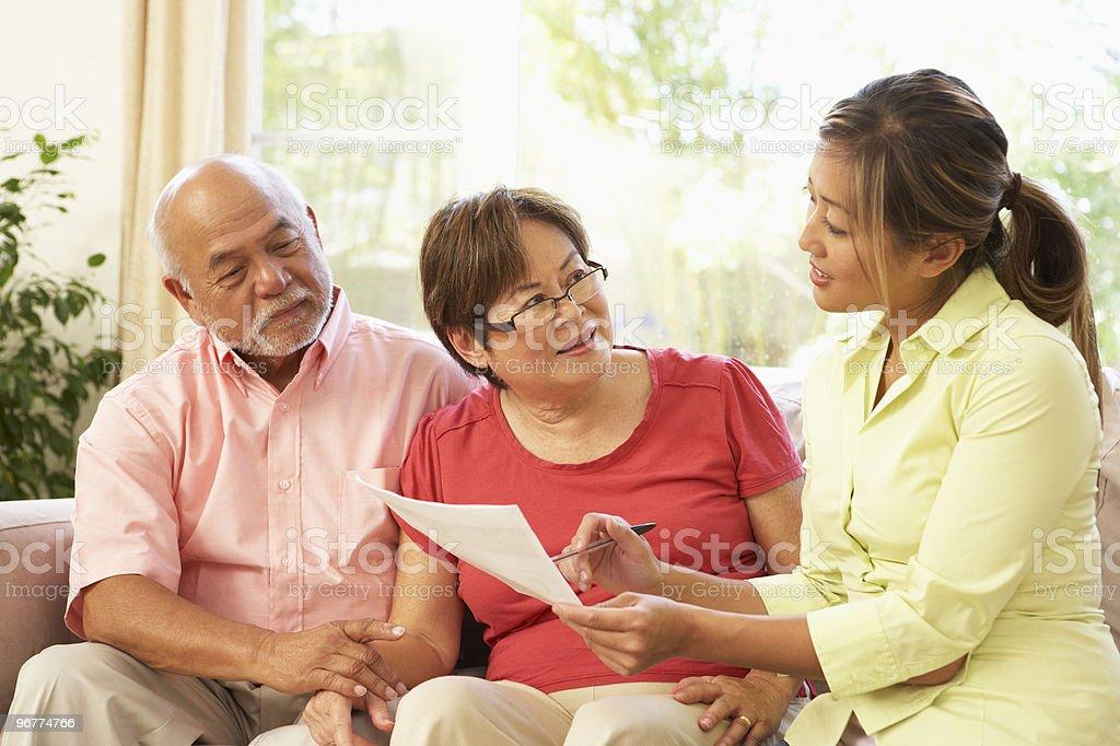 Senior couple receiving financial advice at home stock photo