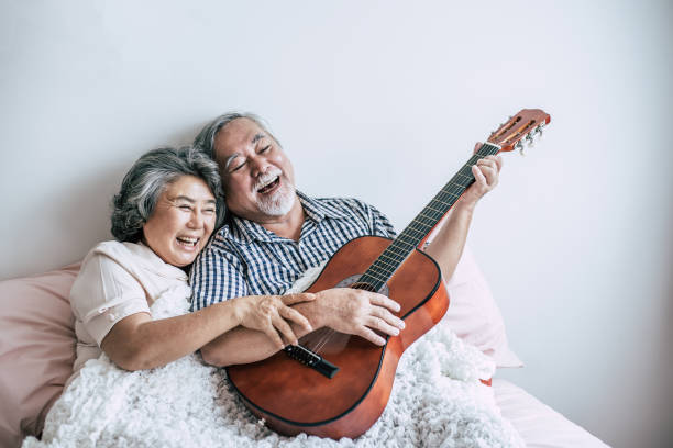 Senior couple  relax playing acoustic guitar in bed room stock photo