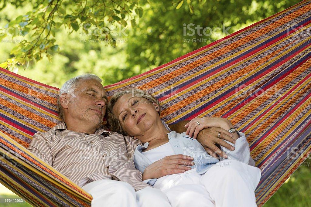 Senior couple relax sleeping in hammock stock photo