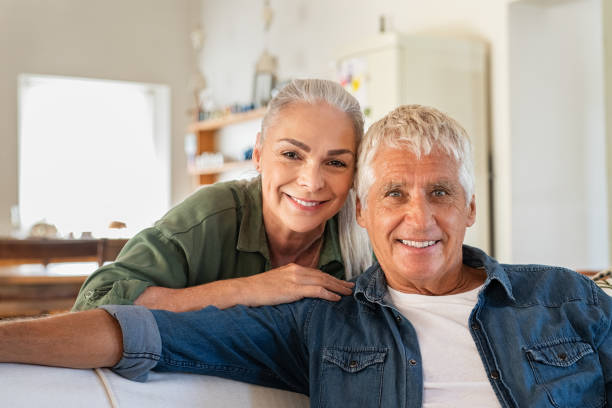 Senior couple relaxing at home Portrait of happy senior couple relaxing at home and looking at camera. Romantic mature woman embrace from behind her smiling old husband. Cheerful senior couple enjoying life and retirement. senior couple stock pictures, royalty-free photos & images