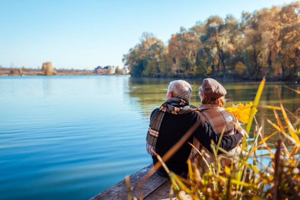 Senior couple relaxing by autumn lake. Happy man and woman enjoying nature and hugging sitting on pier