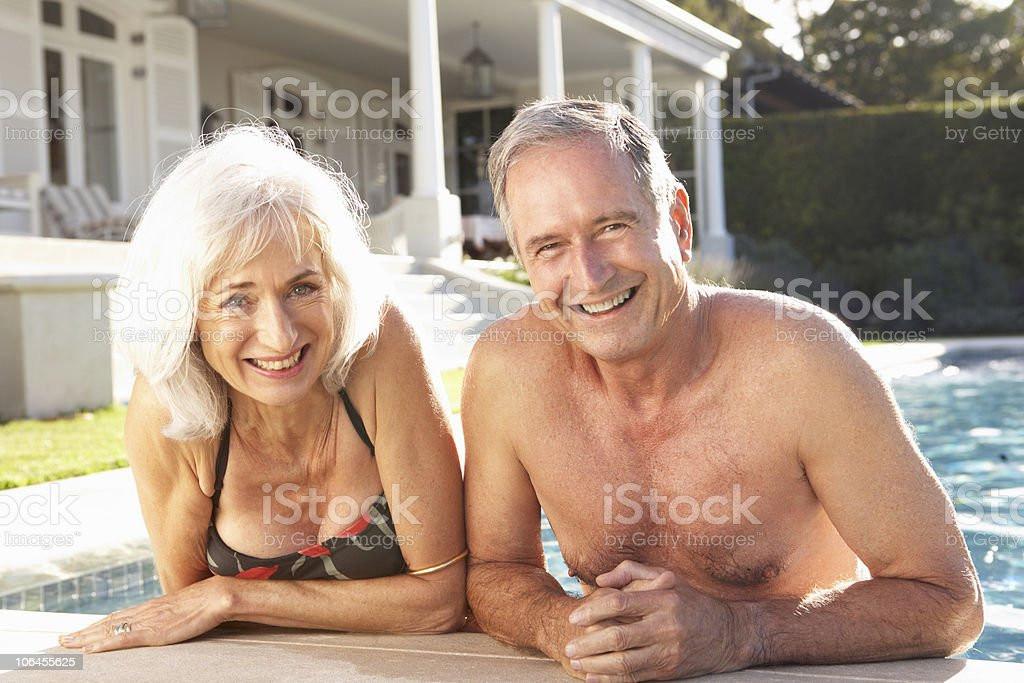 Senior Couple Relaxing by Outdoor Pool royalty-free stock photo