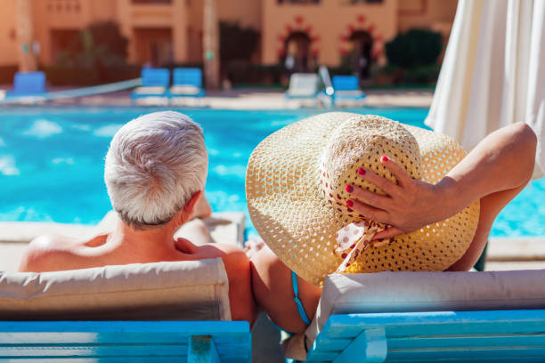 Senior couple relaxing by swimming pool lying on chaise-longues. People enjoying summer vacation. stock photo
