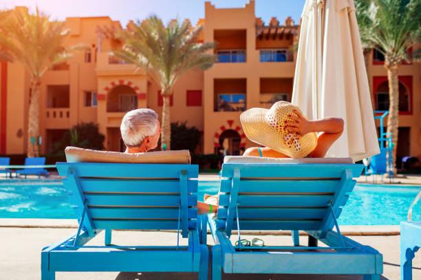 starsza para relaksująca się przy basenie leżącego na szezlongach. ludzie korzystający z letnich wakacji. - kurort turystyczny zdjęcia i obrazy z banku zdjęć