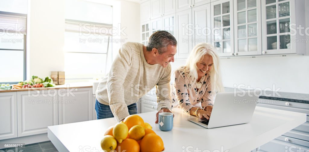 Senior couple relaxing in a kitchen with a laptop stock photo