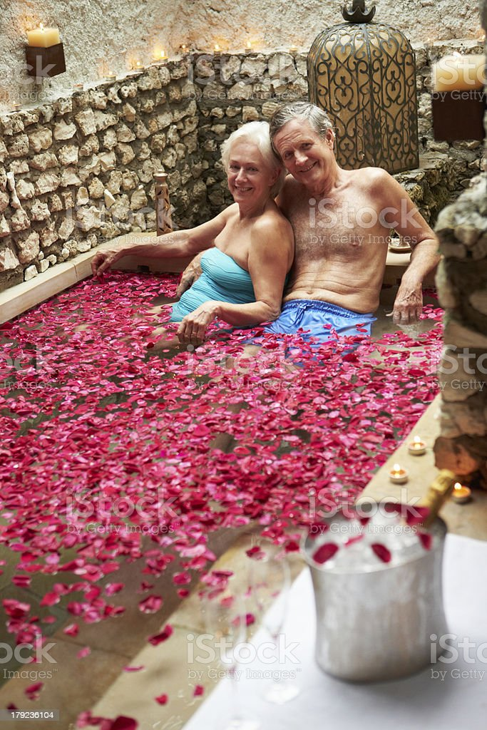 Senior Couple Relaxing In Flower Petal Covered Pool At Spa royalty-free stock photo