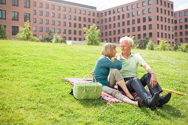 altes paar entspannenden im park - seniorenwohnungen stock-fotos und bilder