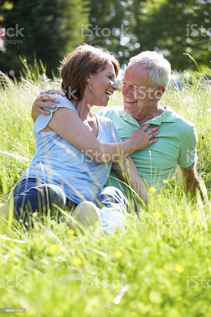 Senior Couple Relaxing In Summer Field Together royalty-free stock photo