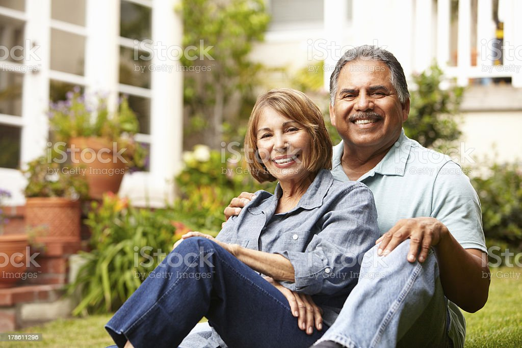A senior couple relaxing in their garden at home stock photo