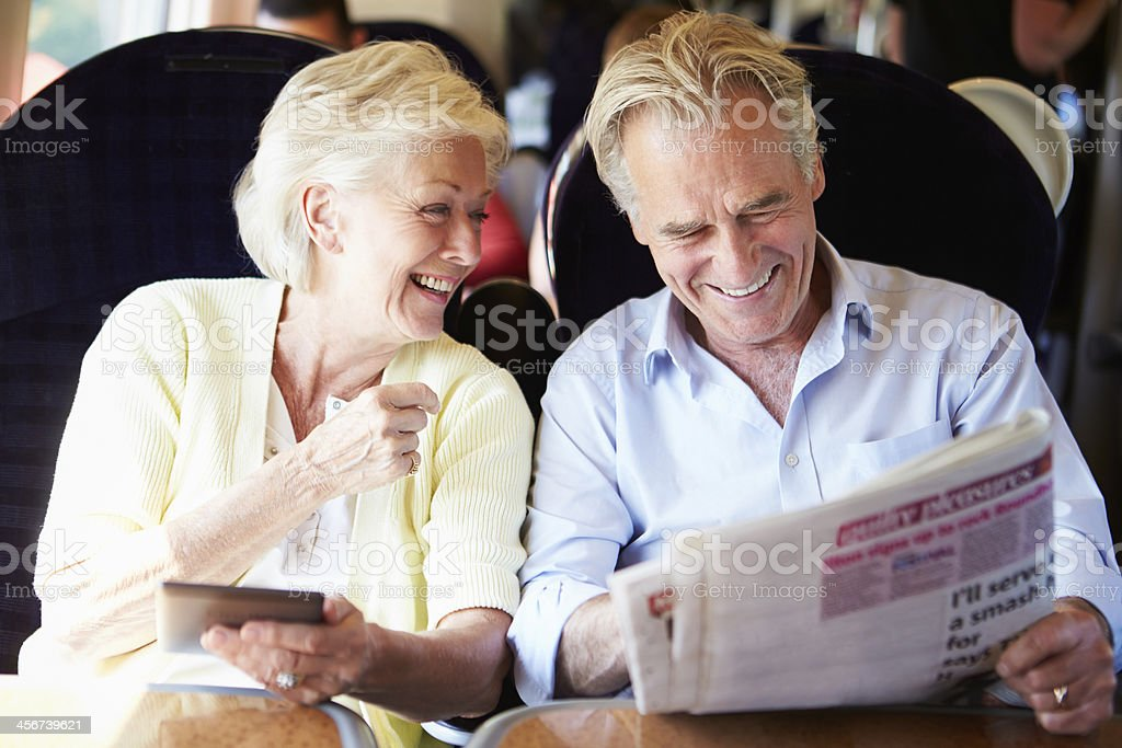 A senior couple relaxing on a train stock photo