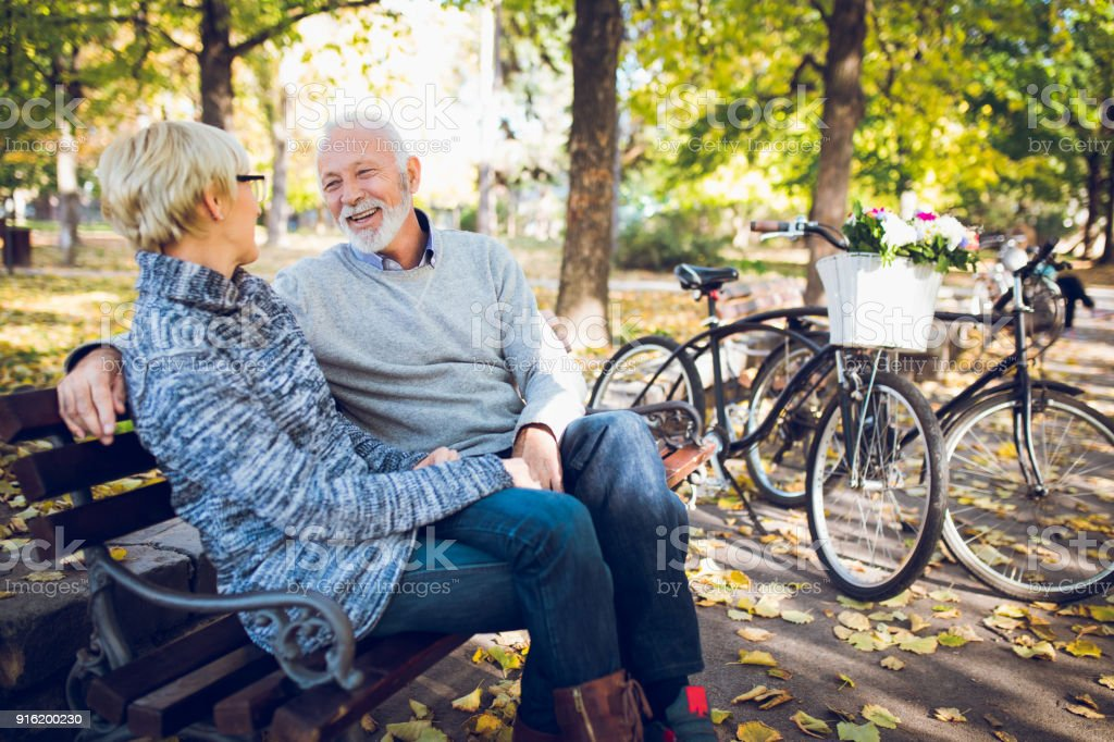 Senior couple relaxing on bench in the park stock photo