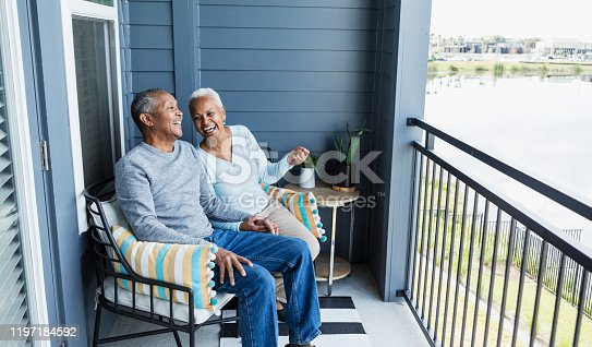 A senior African-American couple sitting side by side on their porch or balcony, relaxing, and holding hands, conversing and laughing together.