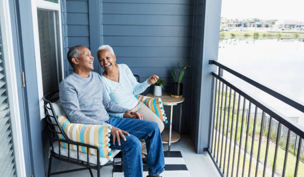 Senior couple relaxing on porch, holding hand, laughing stock photo