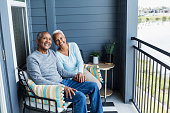 A senior African-American couple sitting side by side on their porch or balcony, relaxing, and holding hands, smiling at the camera.
