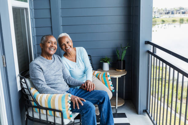 Senior couple relaxing on porch, holding hand, smiling A senior African-American couple sitting side by side on their porch or balcony, relaxing, and holding hands, smiling at the camera. 65 69 years stock pictures, royalty-free photos & images