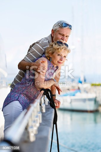 This is an image of senior couple relaxing and sailing on a cruise ship. The man is hugging his wife and they are smiling. In the background we can see the sea and some boats and yachts.