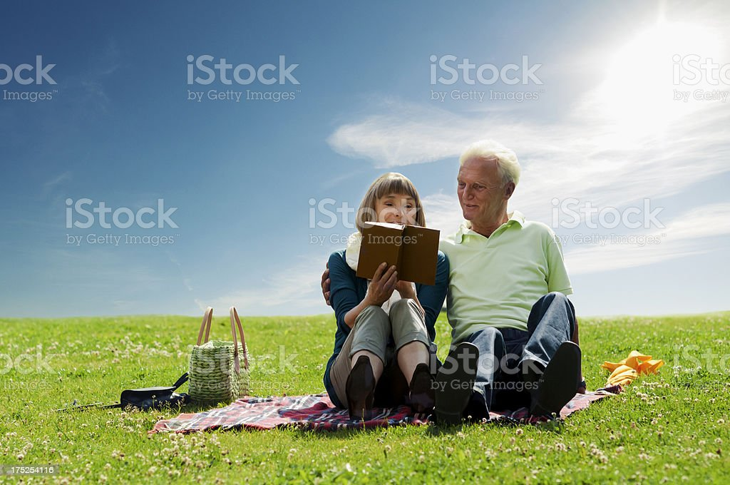 Senior couple relaxing outdoors on the grass royalty-free stock photo