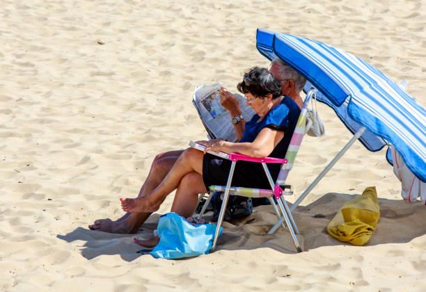 senior paar ontspannen zittend op de strandstoel bij strand - newspaper beach stockfoto's en -beelden